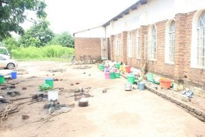 Pots, pans, and buckets lined up outside a brick building