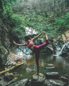 Woman doing yoga by natural pool