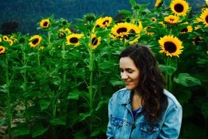 Girl standing by sunflowers