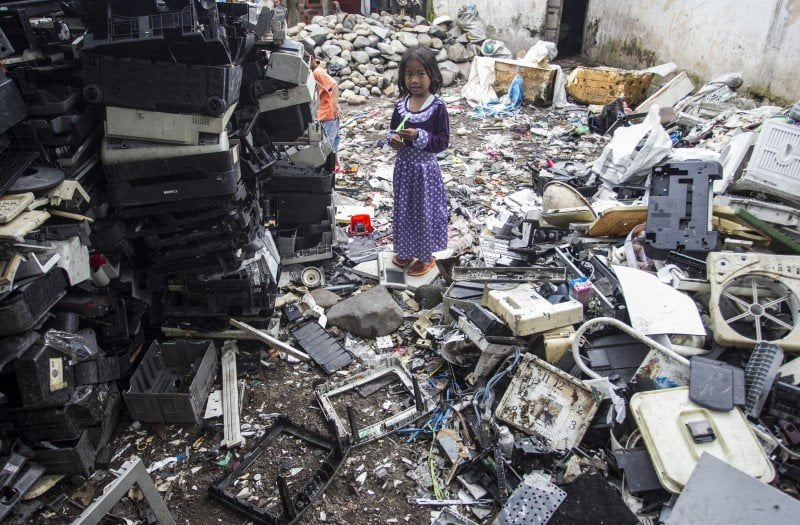 Young girl in third world country surrounded by e waste