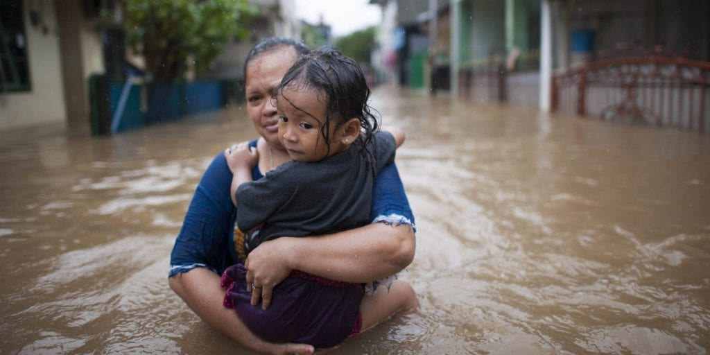 Mother carrying daughter through flooded street