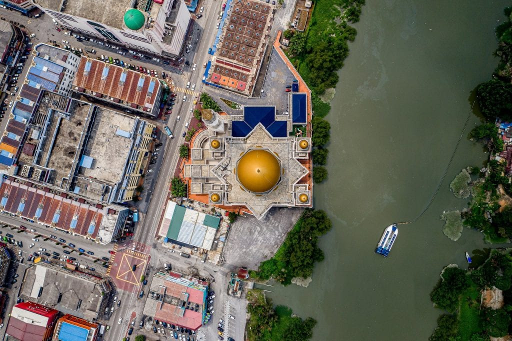 Bird's eye view of a city-side river, and a boat that is part of the ocean cleanup project