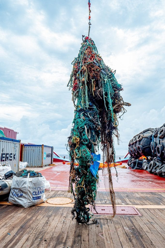 Netting, rope, and other waste is lowered onto the deck of a ship