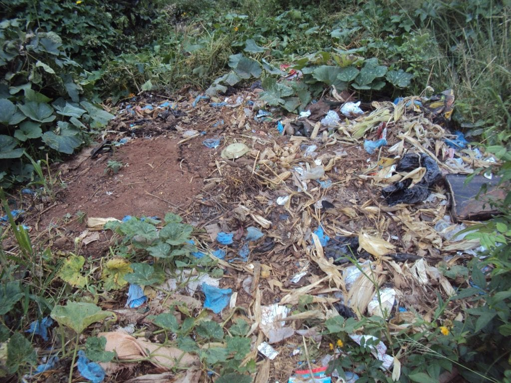 Piles of thin plastic scattered across a dirt mound, with some vegeation struggling to get through