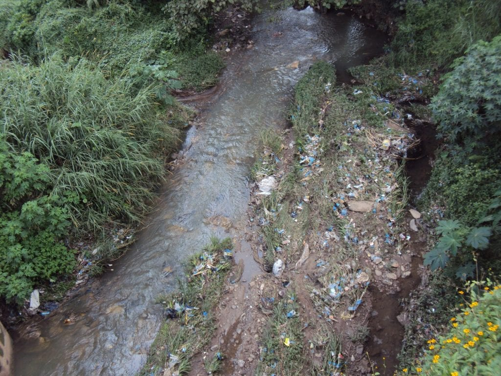 A thin stream, its bank littered with plastic