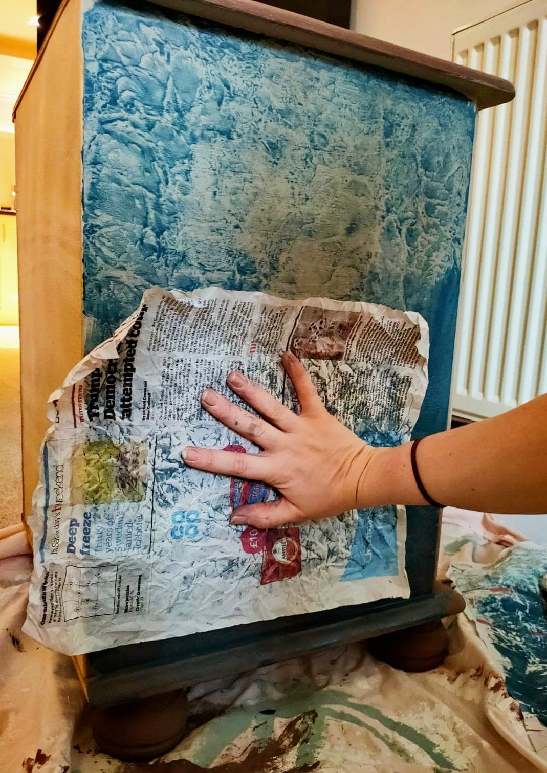 Hand holding newspaper page against drawers