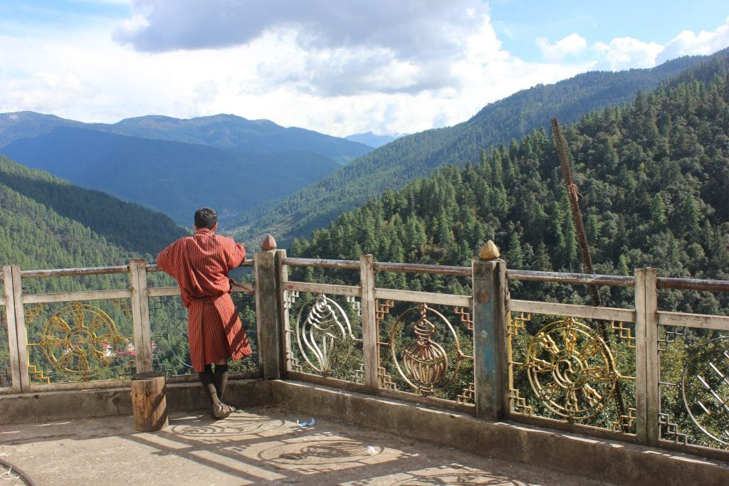 Red robed person standing at an ornate balcony looking out across green forested hills