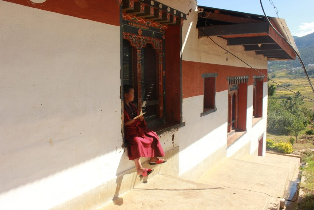 Red robed person sitting on the step of a red and white hillside abode, holding a piece of paper and looking out over green hills