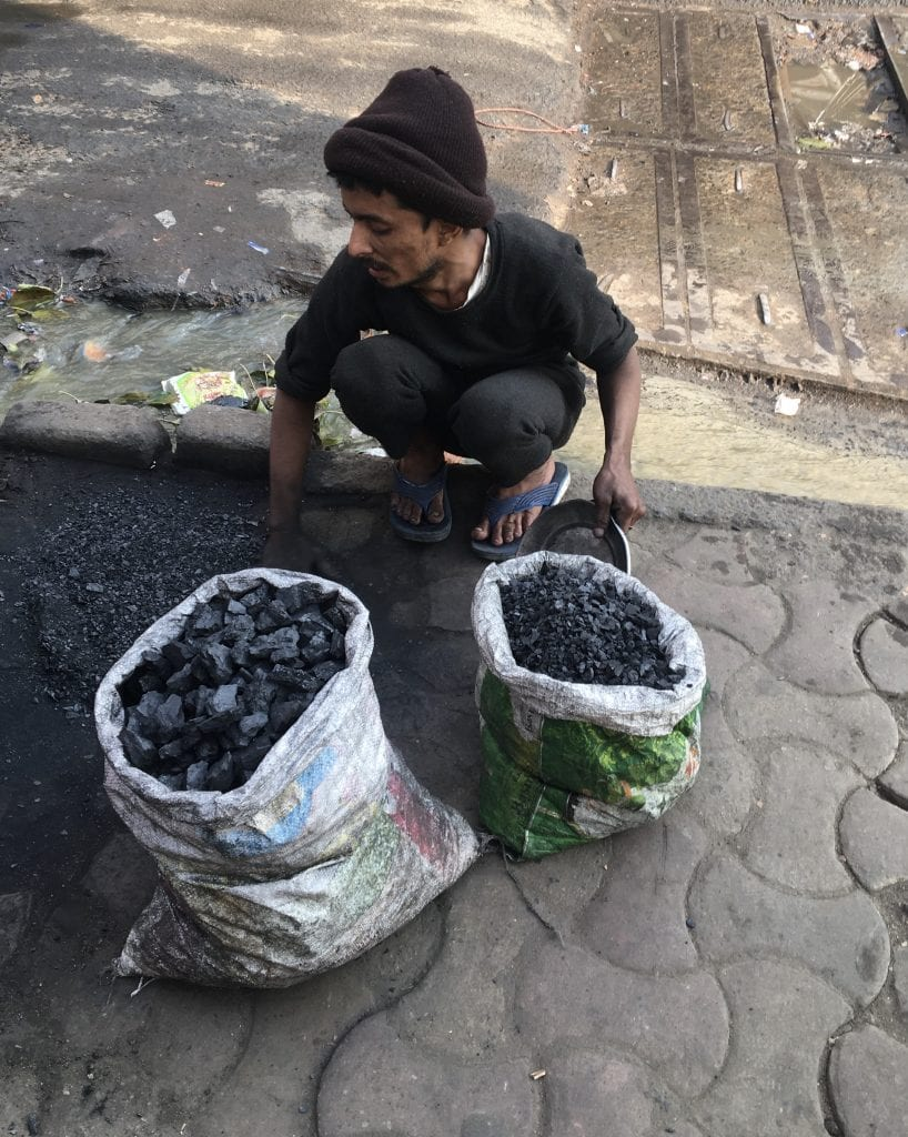 Person crouching over two white sacks filled with palm-sized pieces of black coal, a sign of the need for economic development