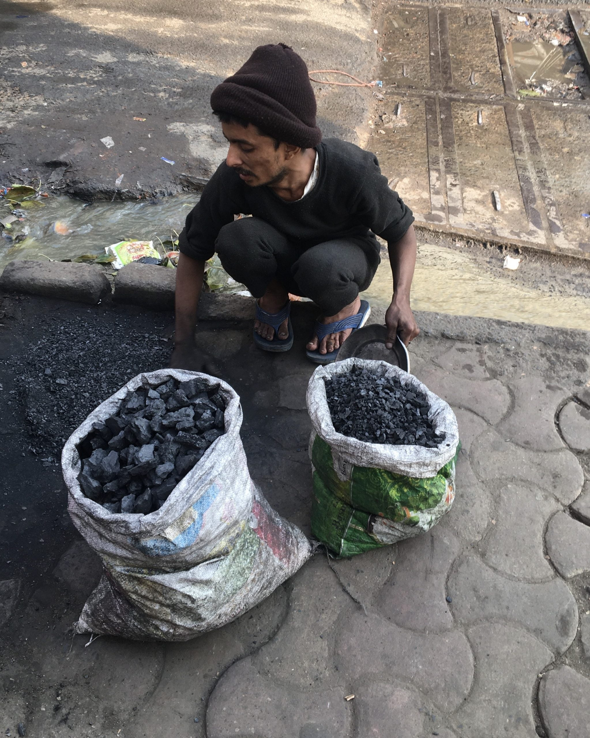 Person crouching over two white sacks filled with palm-sized pieces of black coal