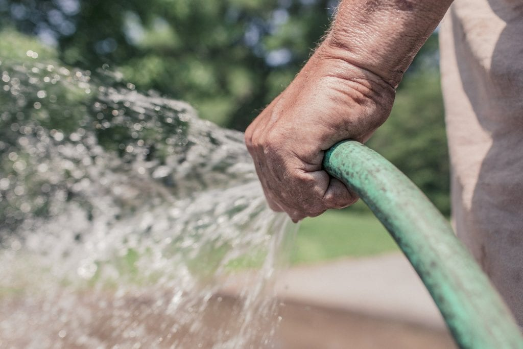 hand holding a hose that is spouting water