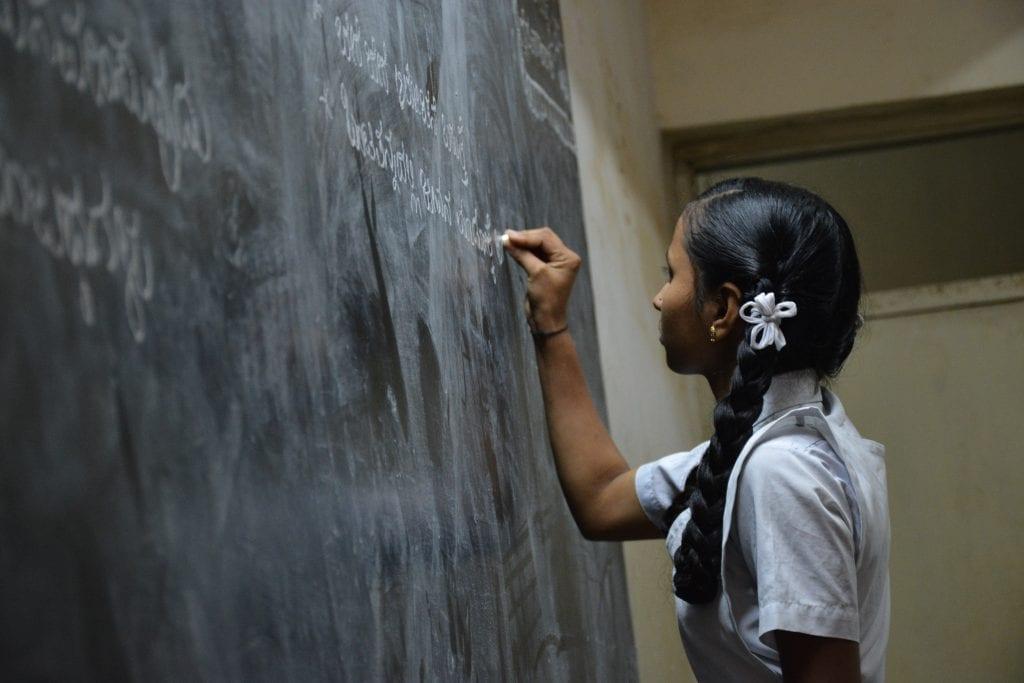 Schoolgirl standing writing on black chalkboard
