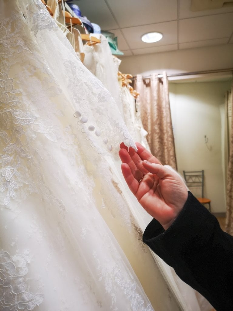 Hand holding the delicate stitching of a wedding dress