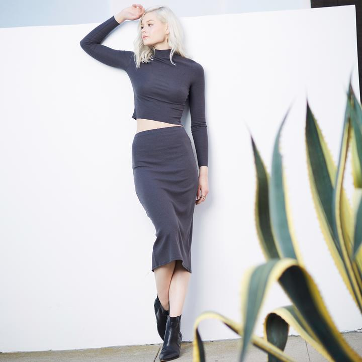 Woman leaning against wall, by Groceries Apparel sustainable activewear