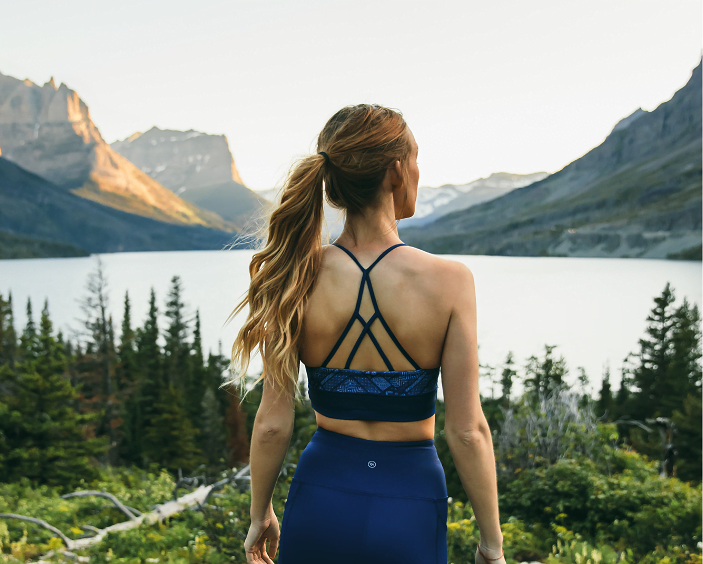 Woman looking out over alpine lake by Kaira, a sustainable activewear brand