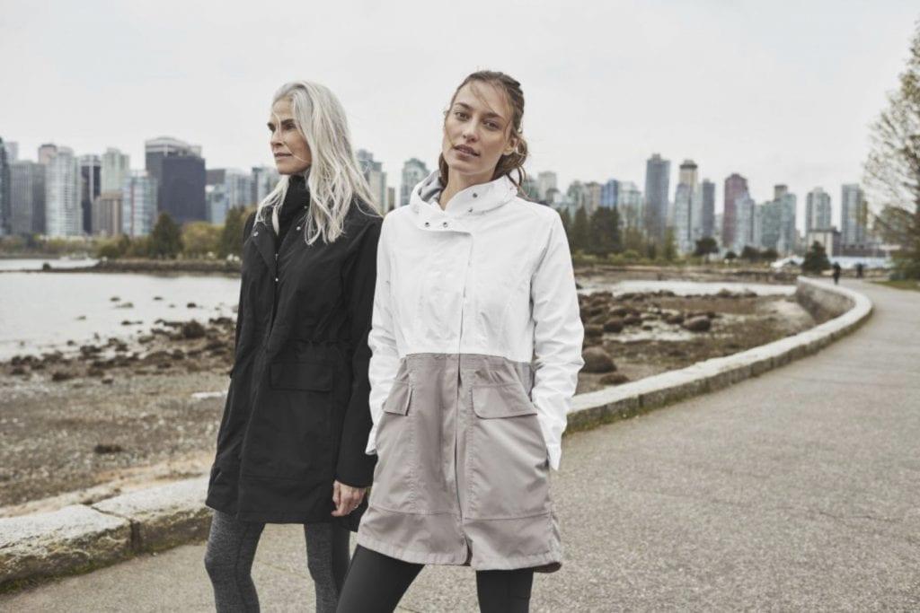 Two women walking along coast, city in background. Outdoor wear by Athleta