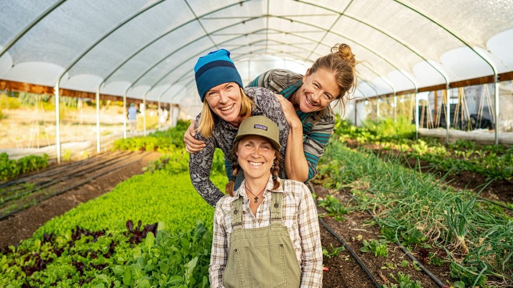 Three happy gardeners in a green house, by Patagonia who also produce sustainable activewear