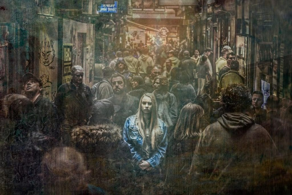 girl in denim jacket standing in a crowd but feeling alone