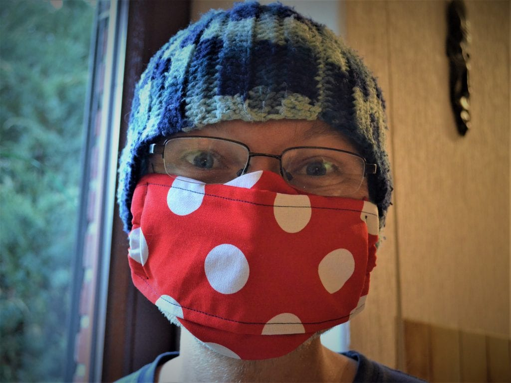 Person wearing large red face mask with white polka dots