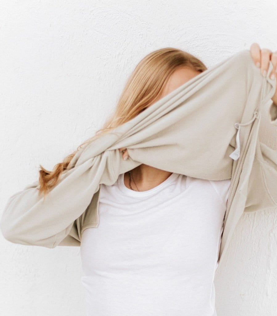 Woman taking off cardigan by Alternative apparel, a sustainable clothing brand
