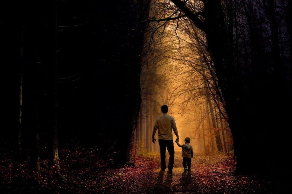 Man holding child's hand as they walk down a forest path