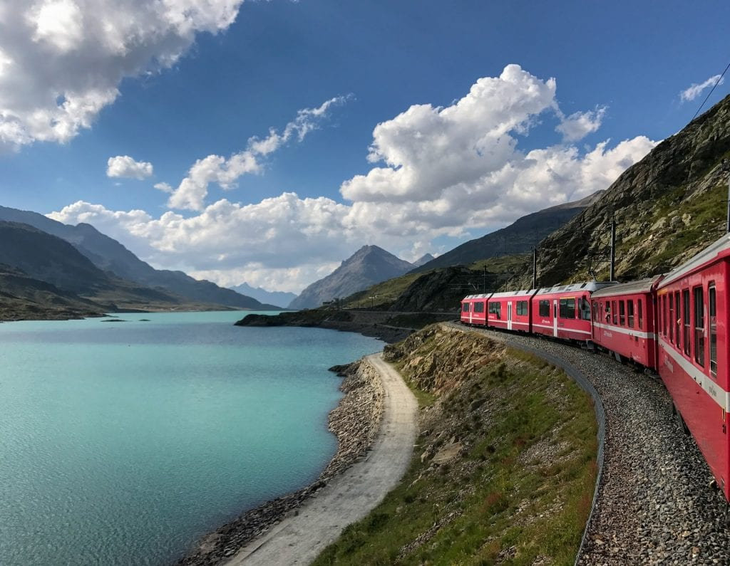 Train passing blue lake in the mountains