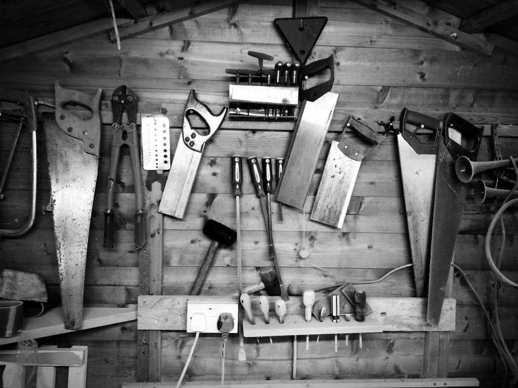 Saws and hand tools on garage wall