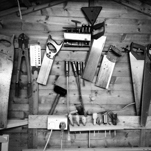 Saws and hand tools on garage wall