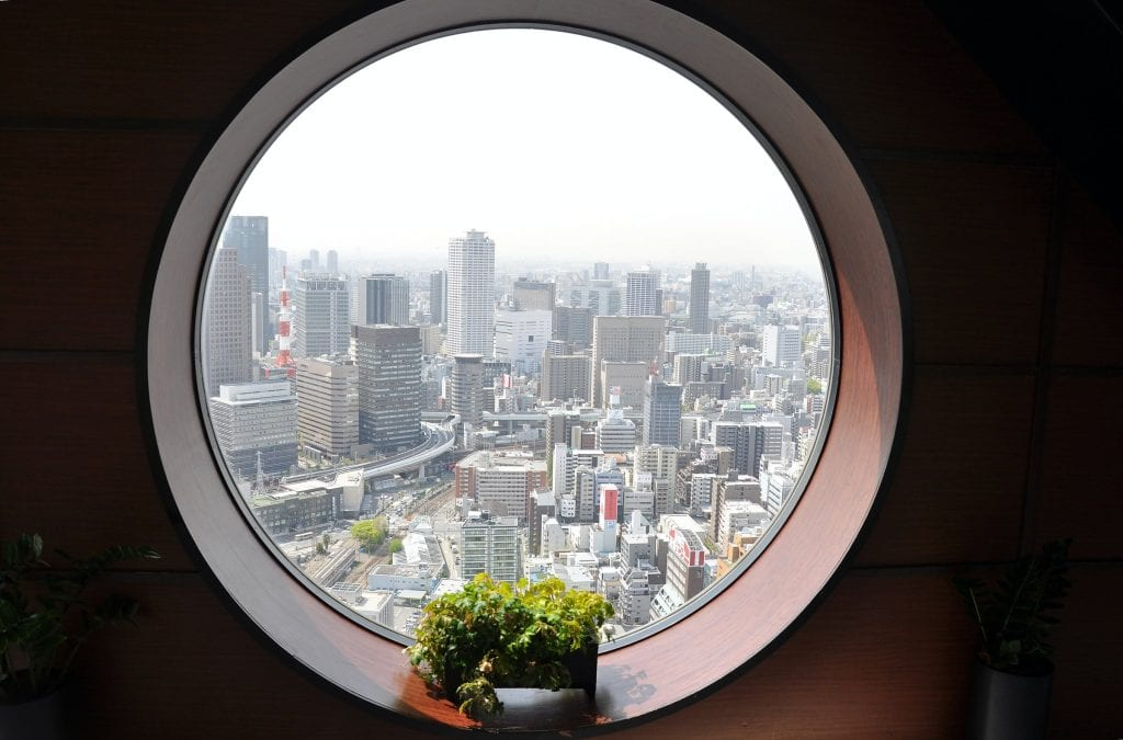 Osaka, Japan seen from inside a round window. Small plant on windowsill.