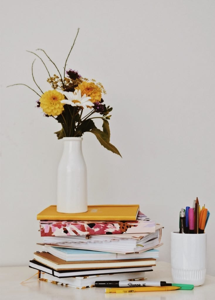 flowers, vase, and books, symbols of sustainability education