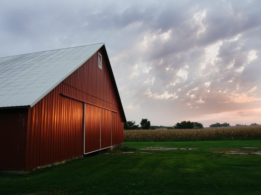A red farm building at dusk: Farms are the key to urban composting