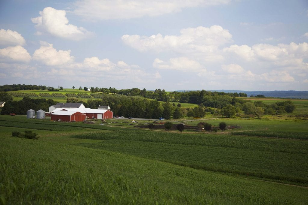 farm in distance with green fields