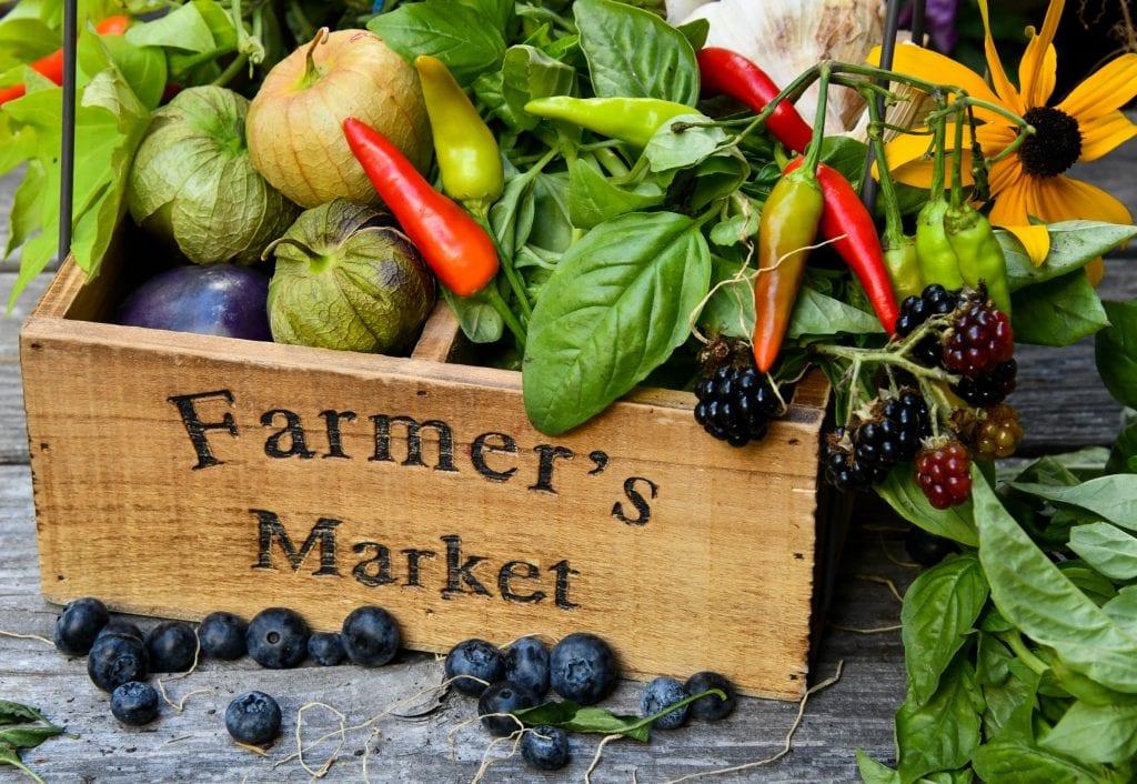 Wooden box labelled 'Farmer's Market' full of vegetables
