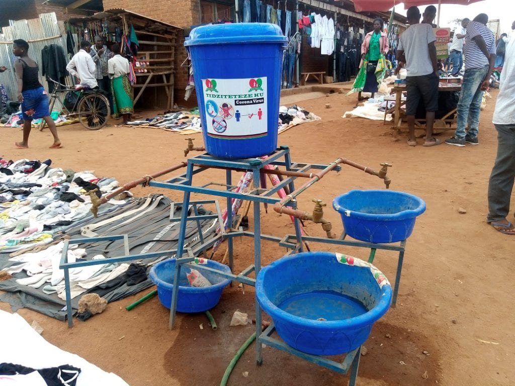 Covid-19 restrictions in Malawi: Blue plastic tubs under tap spouts for handwashing in a sand-floored marketplace