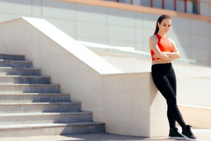 Girl wearing athleisure leaning against stairs