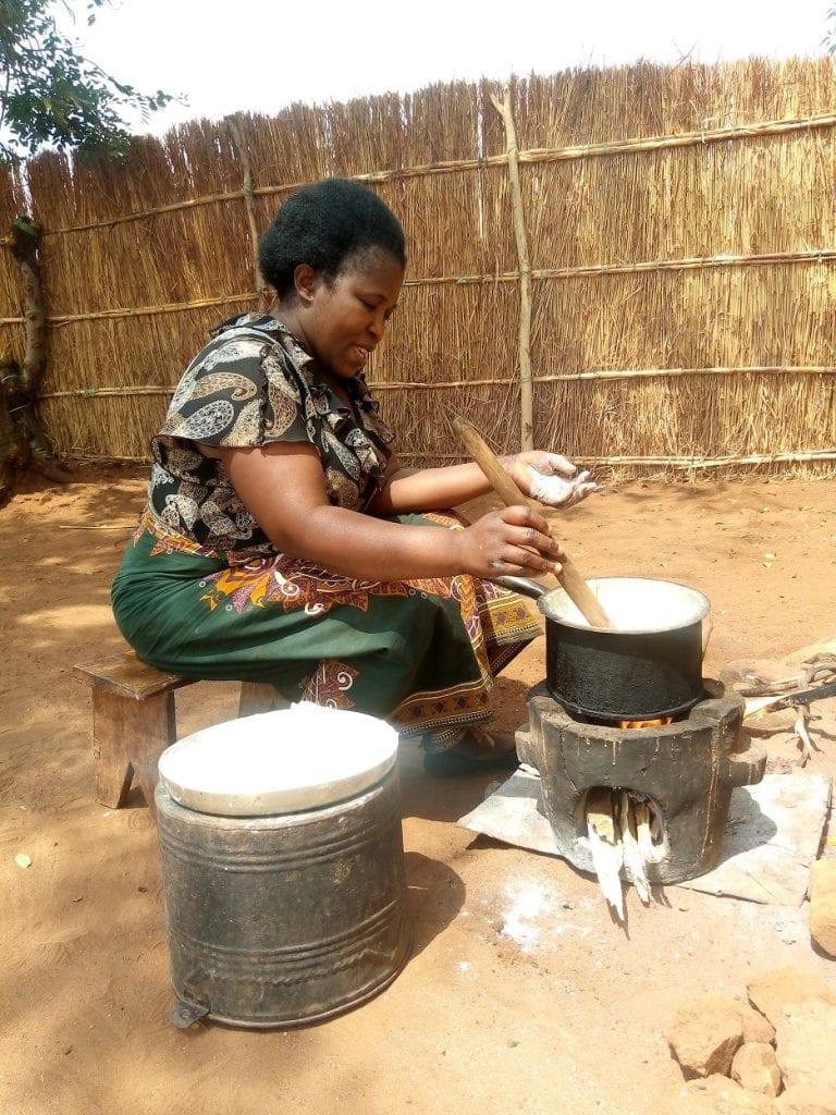 Woman cooking on Chitetezo Mbaula stove