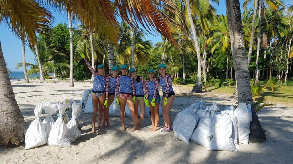 Gloved women after a beach cleanup, with bags of collected waste