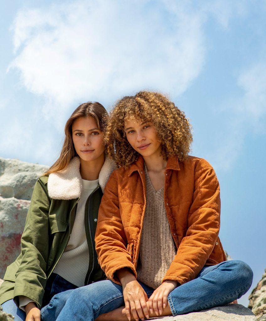two women sitting on a rock