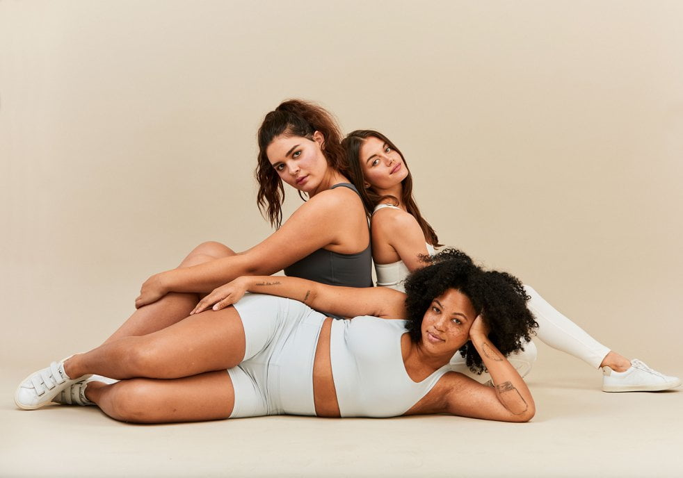 Three women in simple exercise clothing, by Girlfriend Collective sustainable activewear