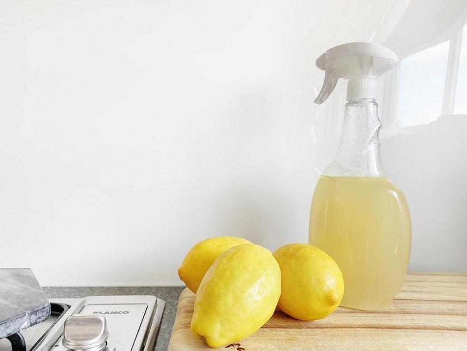 Lemons and spray bottle on wooden chopping board