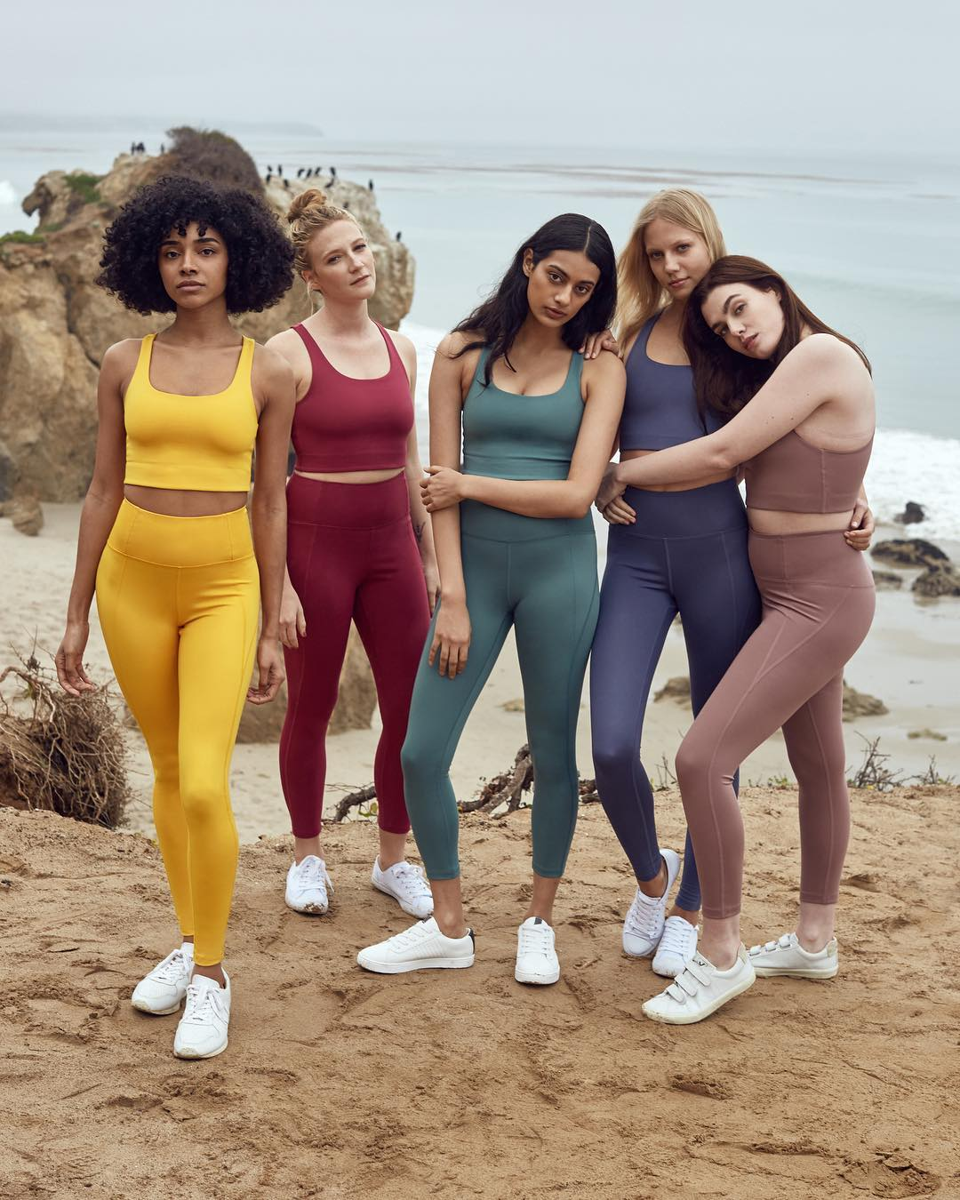 5 women standing on the beach wearing different coloured activewear