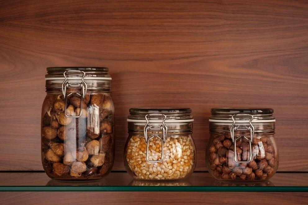 glass jars filled with figs, hazelnuts, and corn kernels