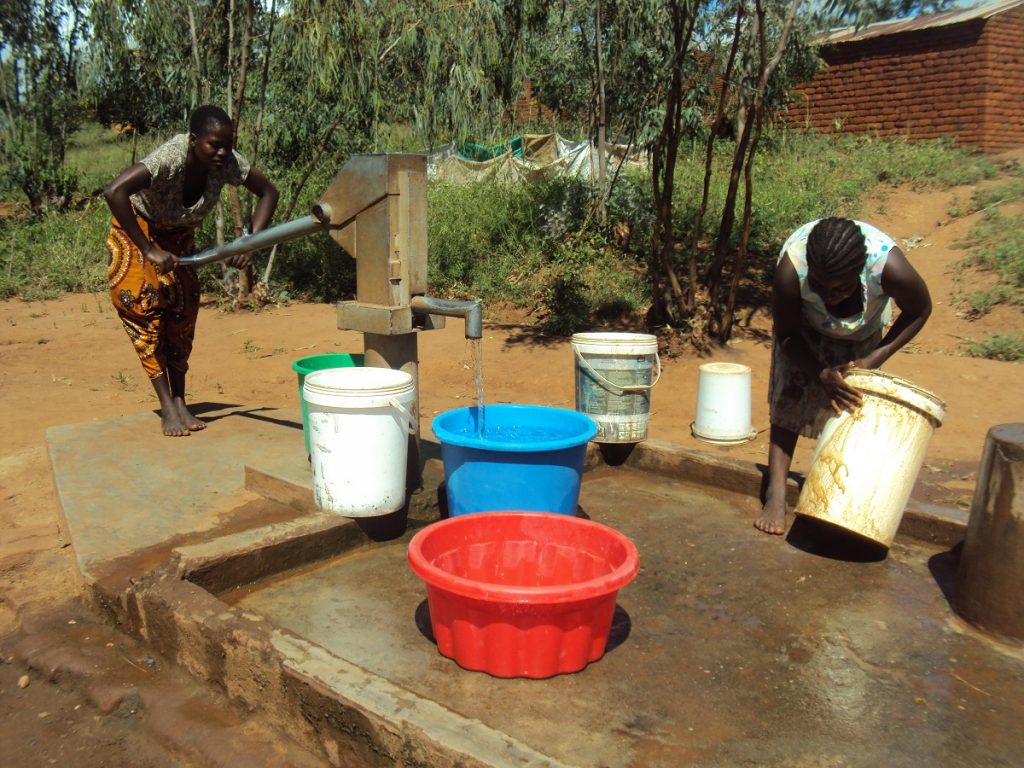 Malawi Water Crisis: Two people filling water containers from a hand-powered pump