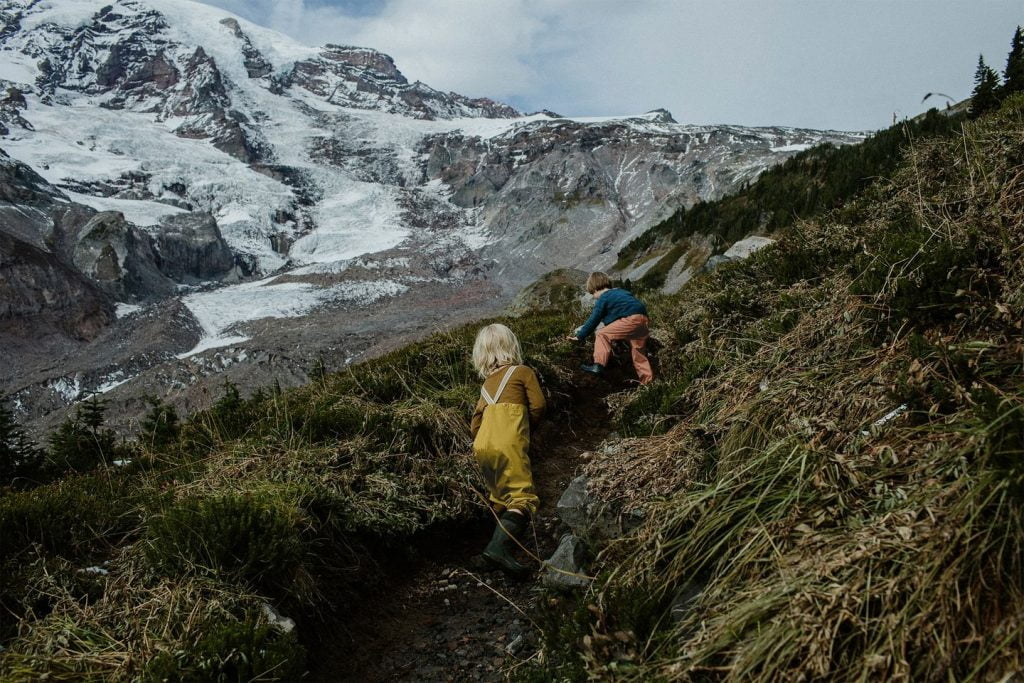 two kids climbing in mountains by Faire Child, a sustainable kids' clothing brand