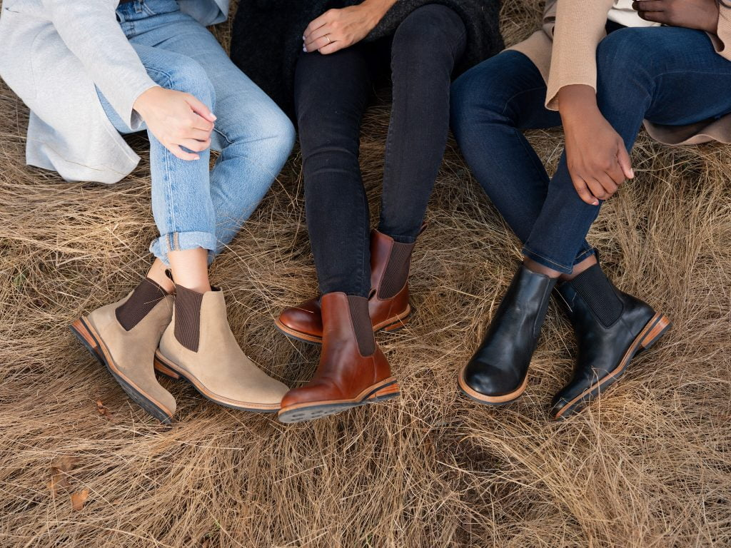 legs of three people in leather boots sitting on hay by Nisolo, a sustainable footwear brand