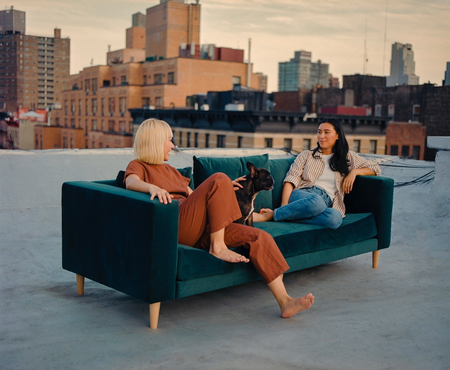 Sustainable furniture & home decor: Two women and a French bulldog sitting on a dark green velvet sofa on a rooftop