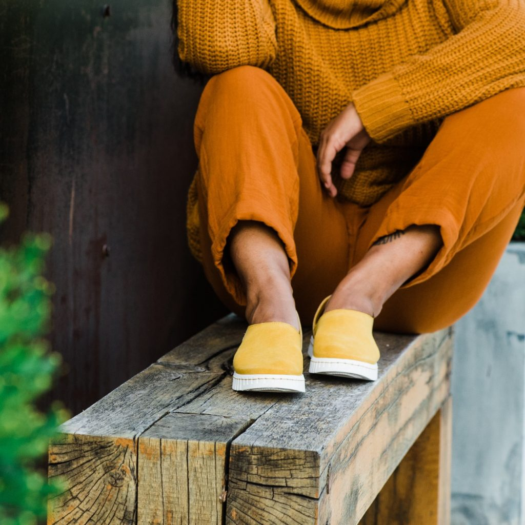 woman sitting on wooden bench by Bendy, a sustainable footwear brand