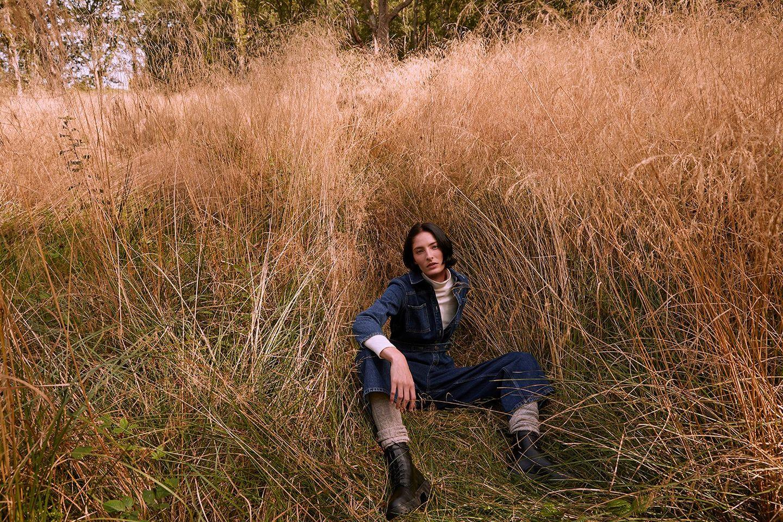 girl sitting amongst tall grass