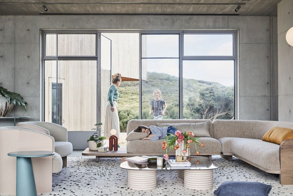 Sustainable furniture & home decor: family in living room with polished concrete floor and view over green hills