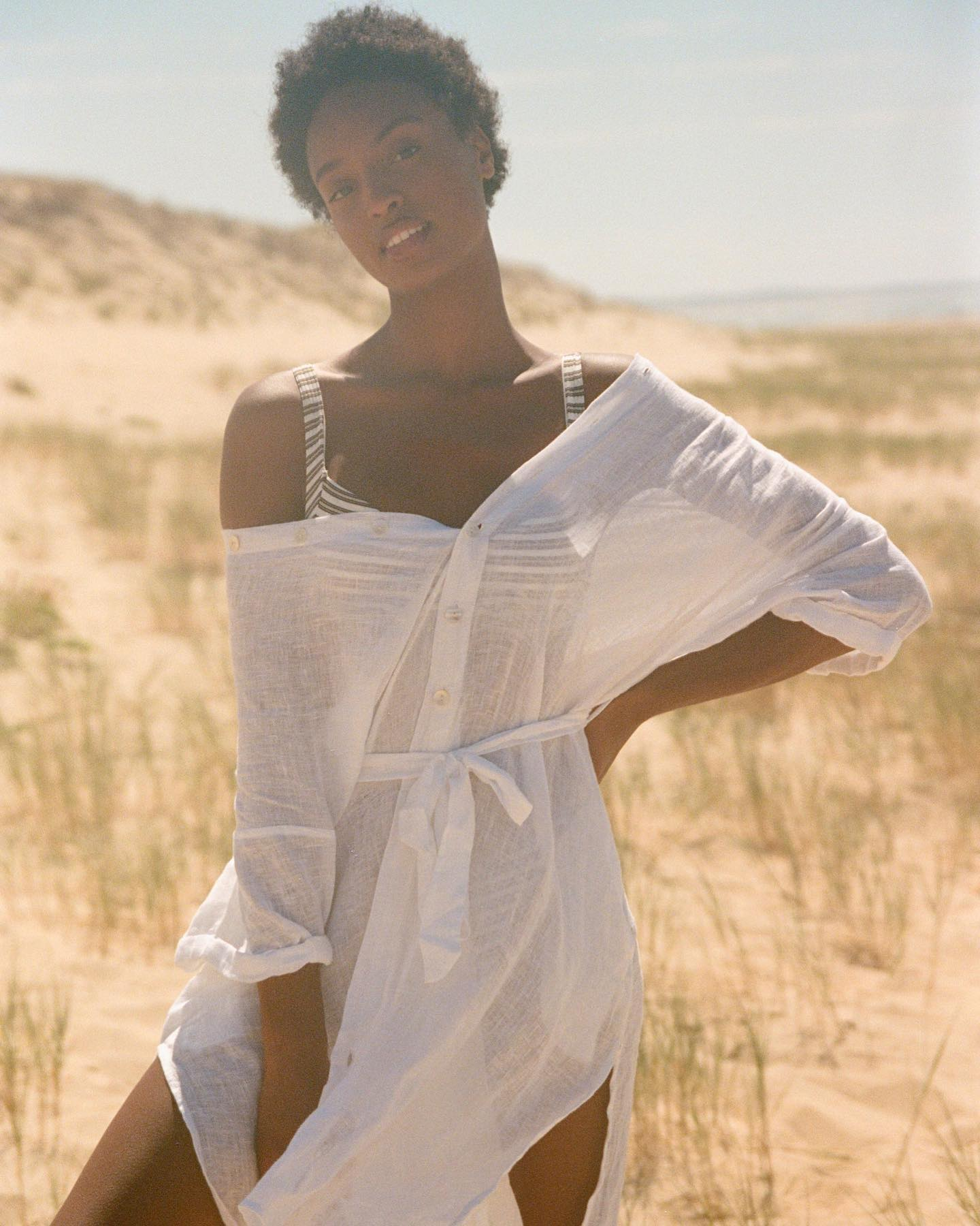 lady in bikini and white top on the beach by Vitamin A, a sustainable clothing brand